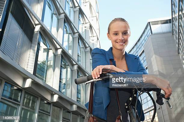 Germany, Bavaria, Teenage girl on bicycle, smiling, portrait