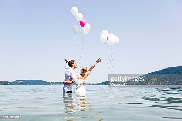 Germany, Bavaria, Tegernsee, Wedding couple standing in lake, holding balloons