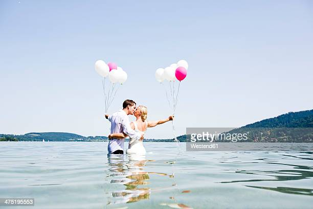 Germany, Bavaria, Tegernsee, Wedding couple standing in lake, kissing