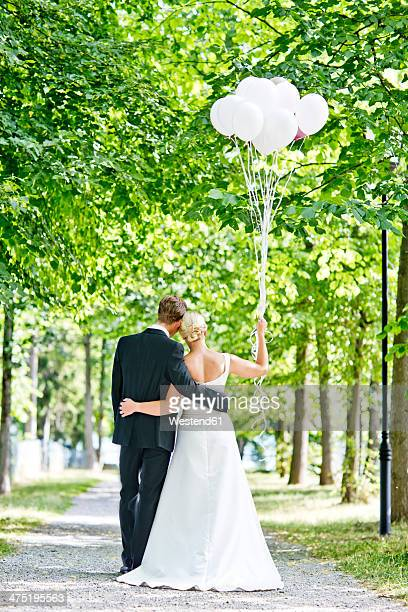 Germany, Bavaria, Tegernsee, Wedding couple walking under trees, holding balloons