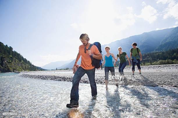 Germany, Bavaria, Toelzer Land, Hikers crossing river