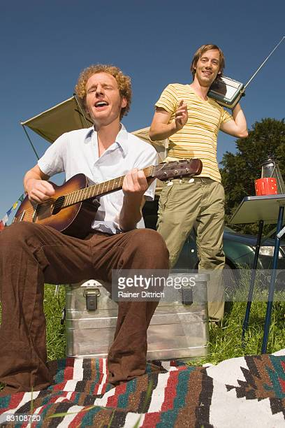 Germany, Bavaria, two men playing guitar and singing