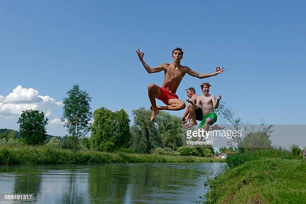 Germany, Bavaria, two teenage boys and man jumping into River Loisach