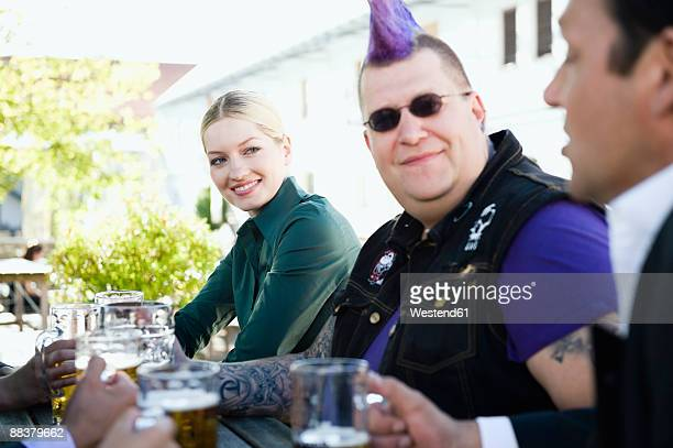 Germany, Bavaria, Upper Bavaria, Business people and punk in beer garden, smiling