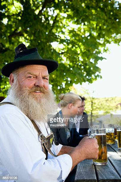 Germany, Bavaria, Upper Bavaria, Man in traditional costume holding beer stein
