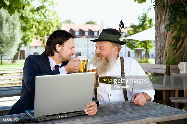 Germany, Bavaria, Upper Bavaria, Senior Bavarian man and young businessman with laptop in beer garden