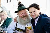 Germany, Bavaria, Upper Bavaria, Senior man and business people in beer garden, smiling, portrait