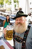 Germany, Bavaria, Upper Bavaria, senior man in beer garden holding beer stein, portrait