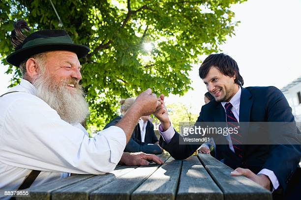 Germany, Bavaria, Upper Bavaria, Two men finger wrestling in beer garden