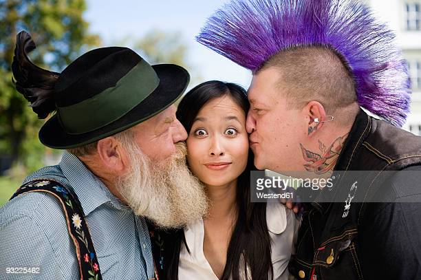 Germany, Bavaria, Upper Bavaria, two men kissing woman on cheek, close-up