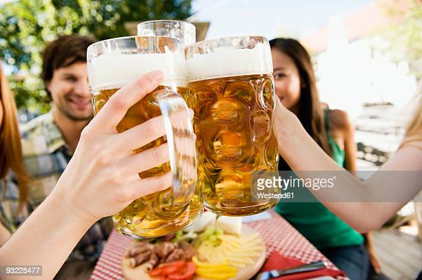 Germany, Bavaria, Upper Bavaria, men and women in beer garden, close-up