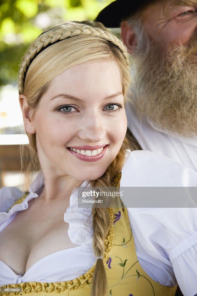 Germany, Bavaria, Upper Bavaria, Young woman in traditional costume, smiling, portrait, close-up
