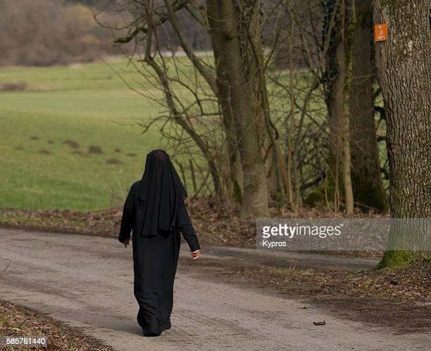Germany, Bavaria, View Of Muslim Woman Wearing Hijab Walking Along Footpath Through Forested Area
