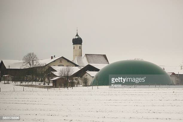Germany, Bavaria, View Of Snow Covered Farmland With Plastic Manure Storage Dome, Church In Background