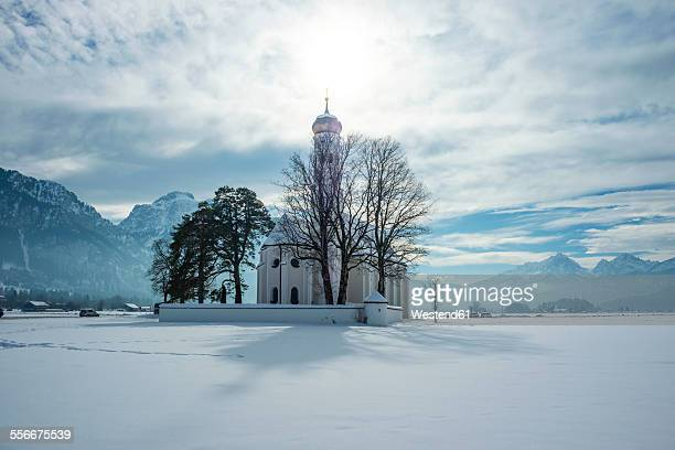 Germany, Bavaria, View of St Coloman Church in front of Tannheim Mountains in winter