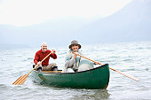 Germany, Bavaria, Walchensee, Senior couple rowing boat on lake, portrait, smiling