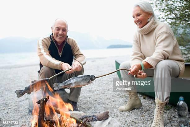 Germany, Bavaria, Walchensee, Senior couple sitting at campfire, grilling fish