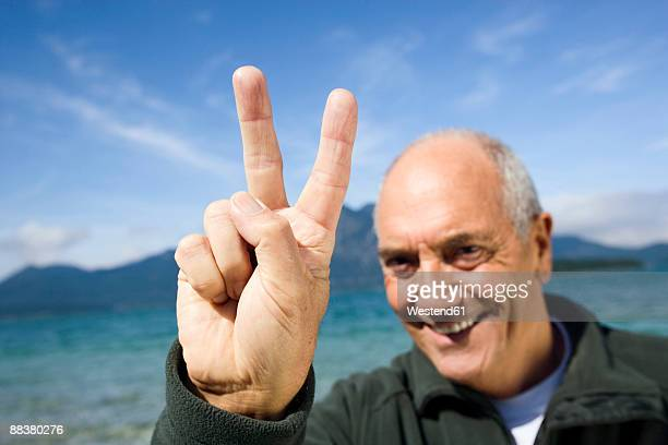 Germany, Bavaria, Walchensee, Senior man showing victory sign, close-up