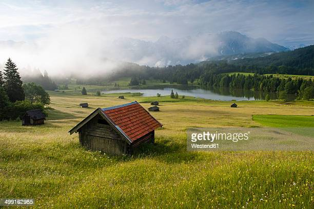 Germany, Bavaria, Werdenfelser Land, lake Geroldsee with hay barn at sunset, in background the Karwendel mountains