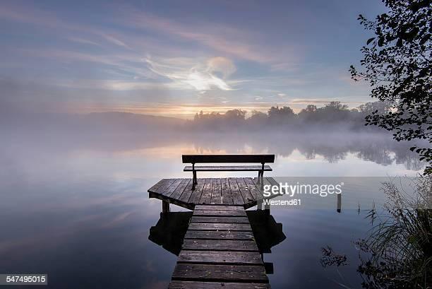 Germany, Bavaria, Wessling, Wesslinger See, boardwalk with wooden bench in the morning mist