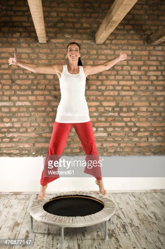 Germany, Bavaria, Woman jumping on trampoline