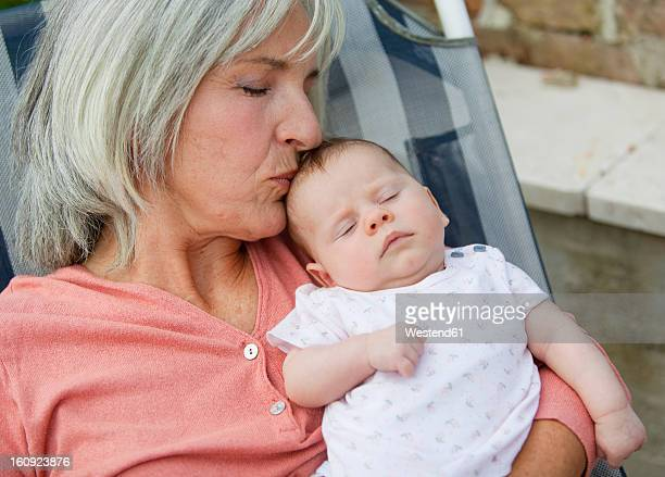 Germany, Bavaria, Woman with grandchild relaxing in lawn chair, smiling