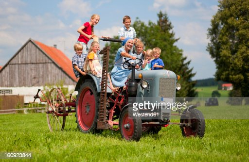 Germany, Bavaria, Woman with group of children sitting on old tractor in front of farmhouse