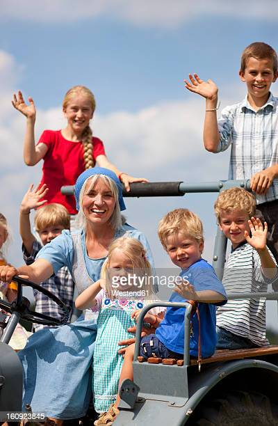 Germany, Bavaria, Woman with group of children sitting on old tractor