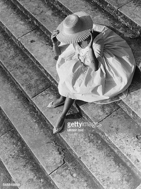 Germany Bavaria woman with sun hat is sitting on the stairs 1950s