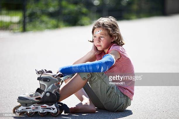 Germany, Bavaria, Wounded girl sitting on road after inline-skating accident