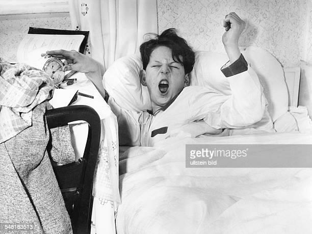 Germany Bavaria yawning boy waking up by a alarm clock