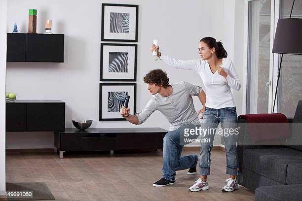 Germany, Bavaria, Young couple playing with game console