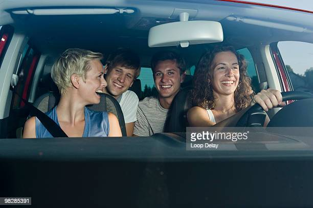 Germany, Bavaria, Friends sitting in car, woman driving, smiling