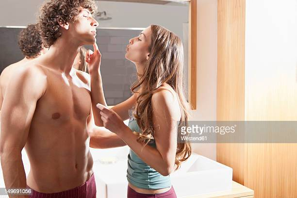 Germany, Bavaria, Young woman applying cream on man face in bathroom