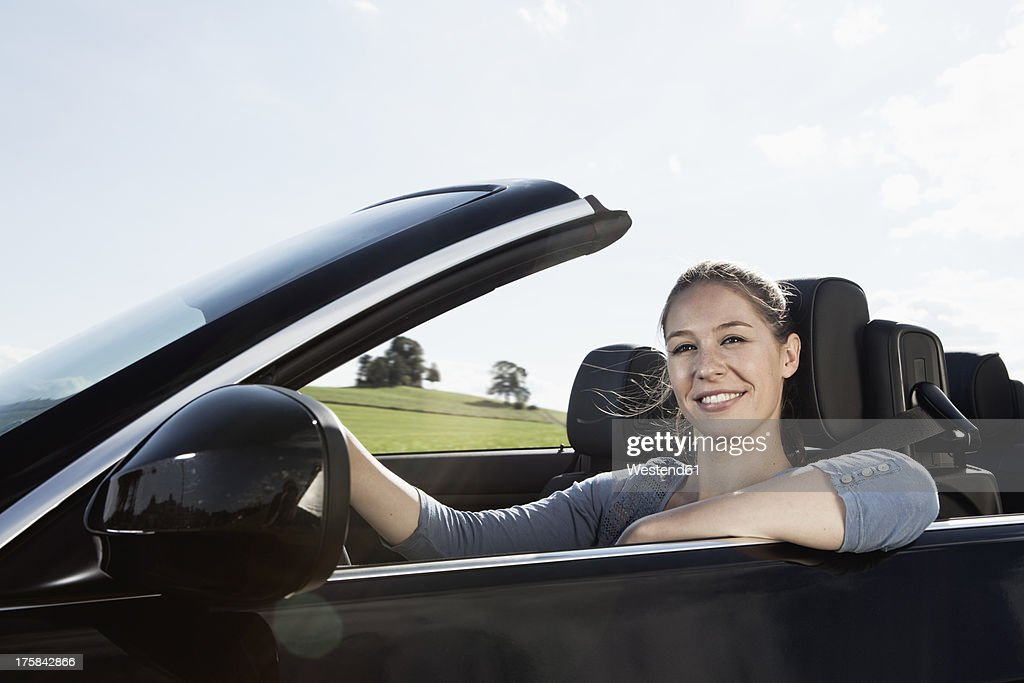 Germany, Bavaria, Young woman in car, smiling