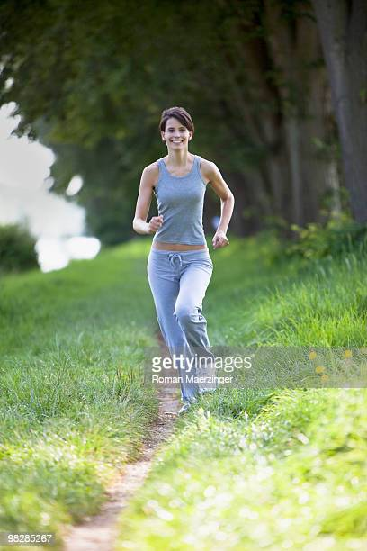 Germany, Bavaria, Young woman jogging, smiling, portrait