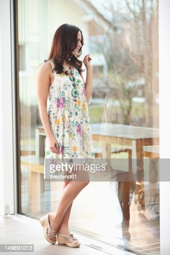 Germany, Bavaria, Young woman looking away, smiling