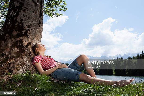 Germany, Bavaria, Young woman lying on grass under tree