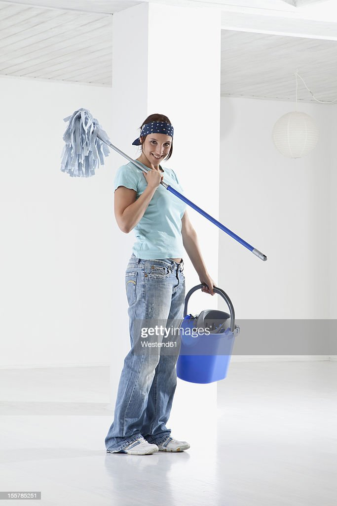 Germany, Bavaria, Young woman mopping floor, smiling, portrait : Stock Photo