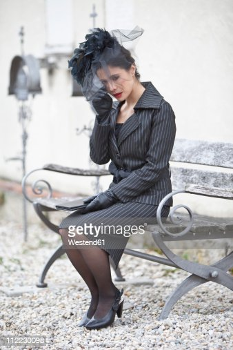 Germany, Bavaria, Young woman sitting on bench and crying