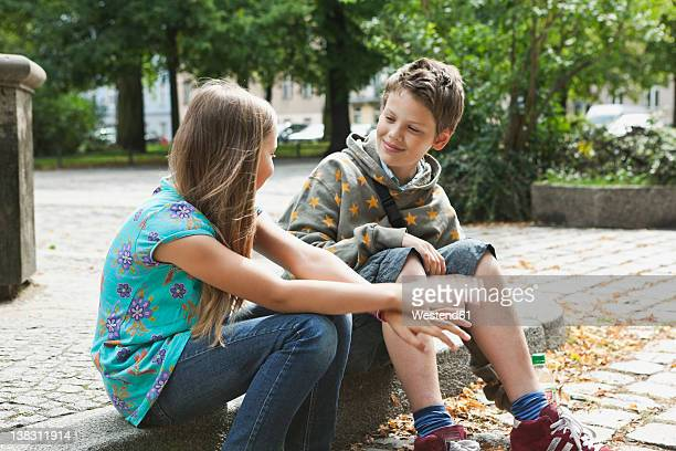 Germany, Berlin, Boy and girl sitting on curbstone
