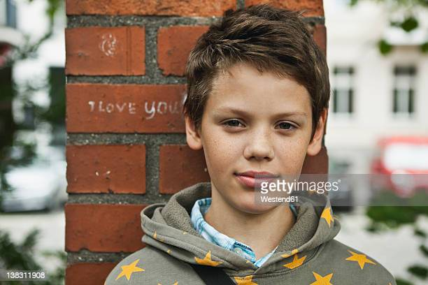 Germany, Berlin, Boy sitting in front of red brick wall