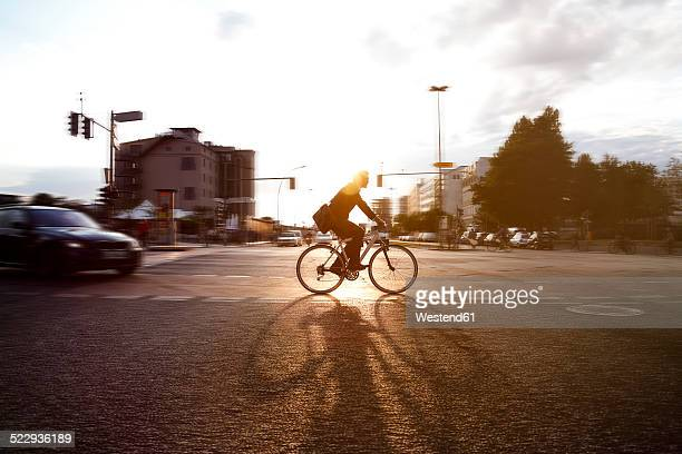 Germany, Berlin, Businessman cycling in the city