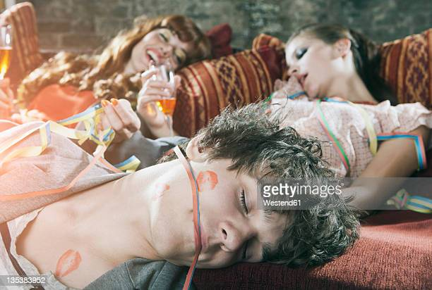Germany, Berlin, Close up of young man and women relaxing on couch after party