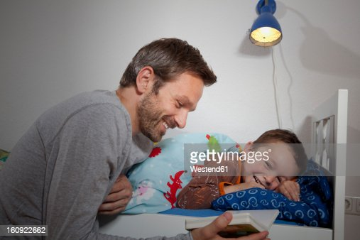 Germany, Berlin, Father reading book while son sleeping