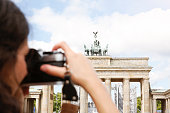 Germany, Berlin, female tourist photographing Brandenburg Gate