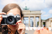 Germany, Berlin, female tourist standing in front of Brandenburg Gate photographing viewer