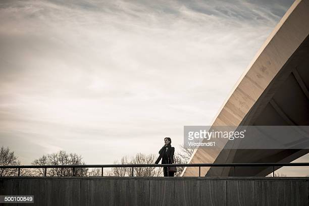 Germany, Berlin, female tourist standing on terrace of House of World Cultures looking at view
