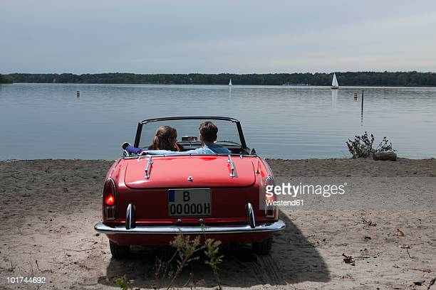 Germany, Berlin, Lake Wannsee, Young couple in cabriolet looking at lake, rear view