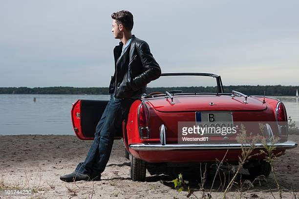Germany, Berlin, Lake Wannsee, Young man standing by car, looking over water, portrait
